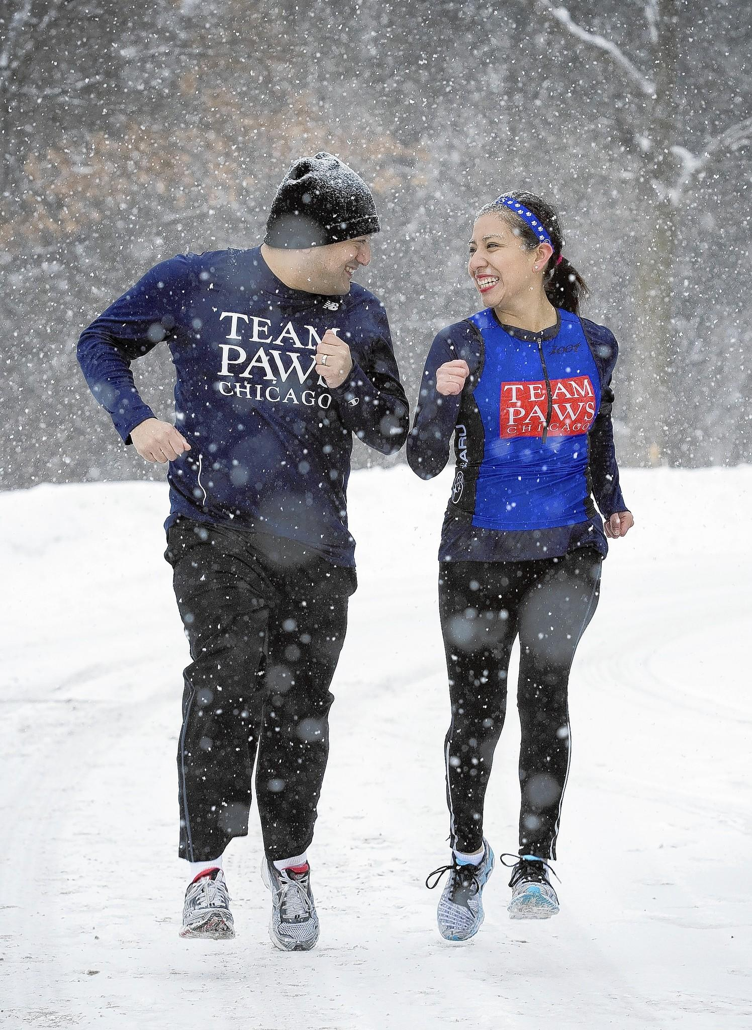 Lionel and Daniela Garcia of Round Lake take a snowy jog near their home on Saturday, Feb. 8, 2014. The Garcias are die-hard runners and newlyweds. After their January wedding at Disney World, they ran a marathon.
