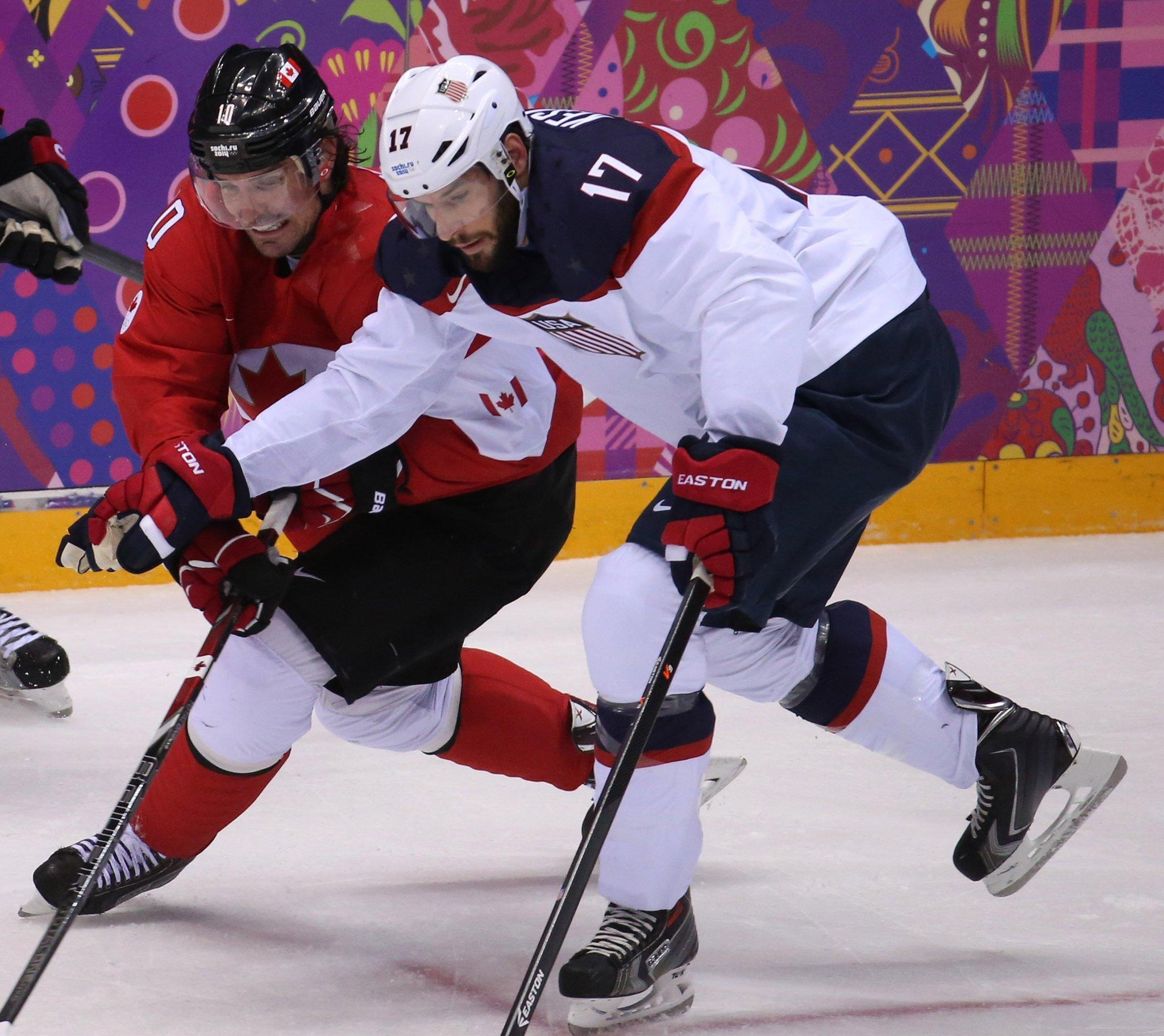 Canada forward Patrick Sharp (left) and U.S. forward Ryan Kesler fight for the puck during Friday's game.