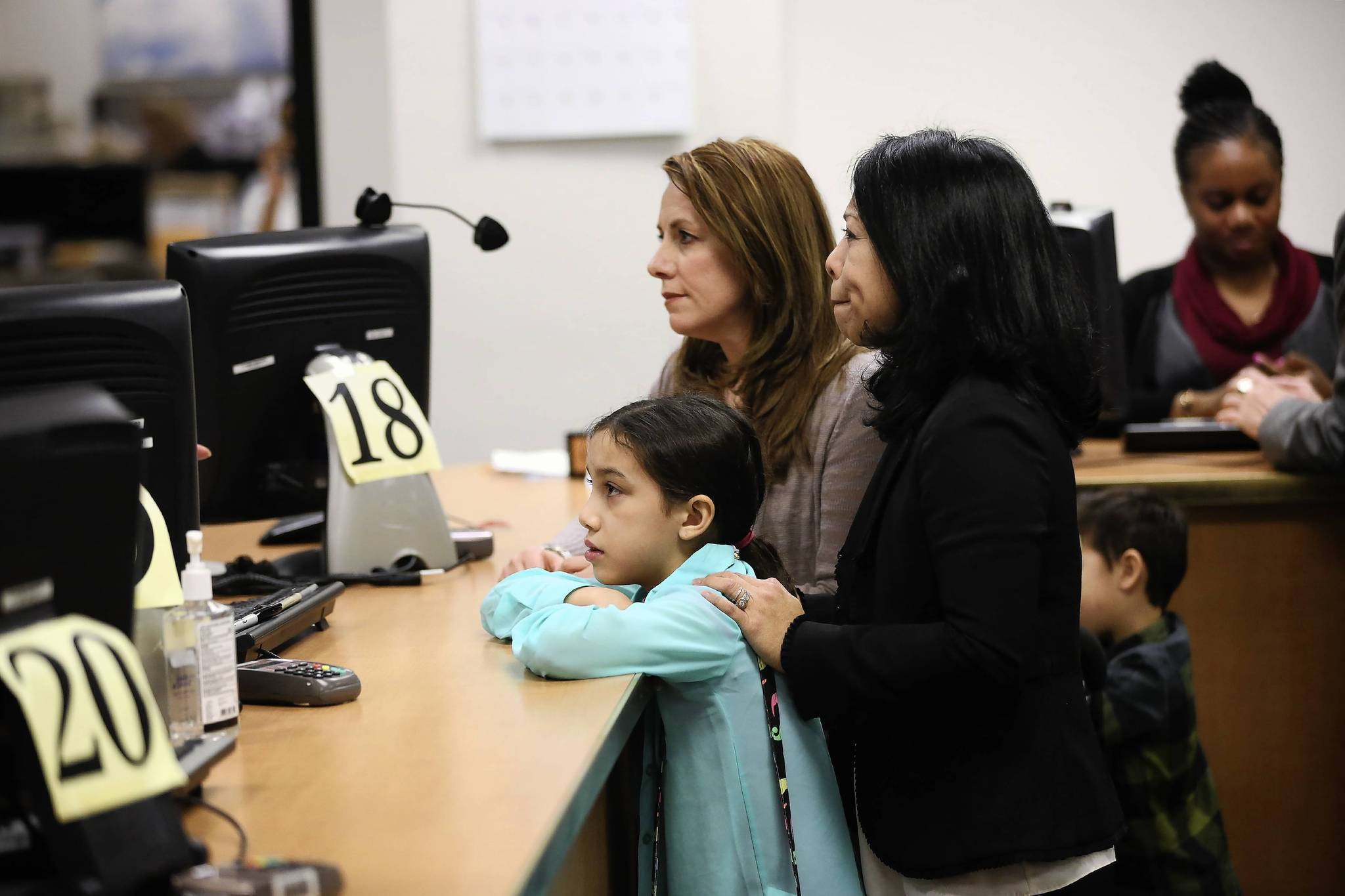 Theresa Volpe (left) and Mercedes Santos and their daughter Ava, 9, wait to be issued a marriage license at the Cook County bureau of Vital Records by Cook County immediately following a federal court order that couples should not have to wait until the Illinois law goes into effect on June 1. The couple were the first to be married after a judge waived the 24 hour waiting period.