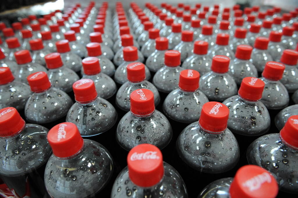 Coca-Cola bottles on an assembly line at a bottling plant.