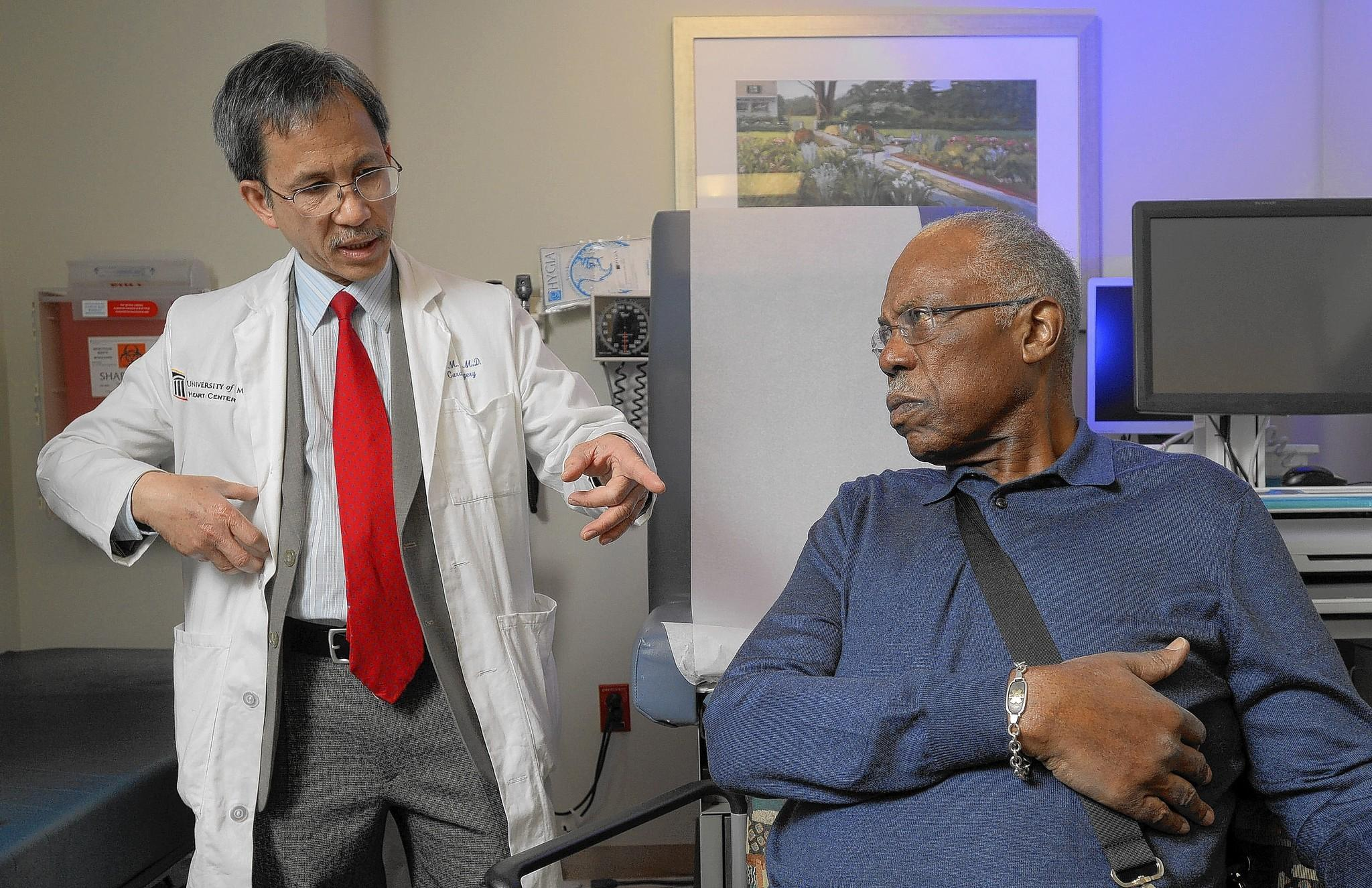 "Dr. Si Pham and patient Walter Amprey, chat in an exam room at the University of Maryland Medical Center. ""I recognize I'm fortunate to be alive,"" Amprey said. ""God has taken care of me so far -- God and Dr. Pham."""
