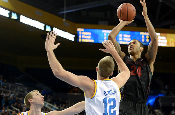 Stanford forward Josh Huestis elevates for a shot over UCLA forwards David Wear (12) and Travis Wear during their game earlier this season at Pauley Pavilion.