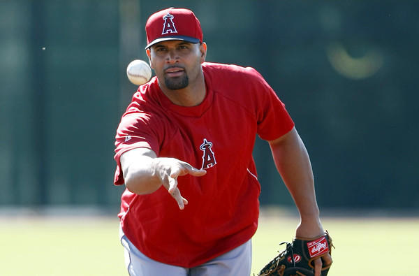 Angels first baseman Albert Pujols tosses the ball to first base during a spring training workout Thursday in Tempe, Ariz.