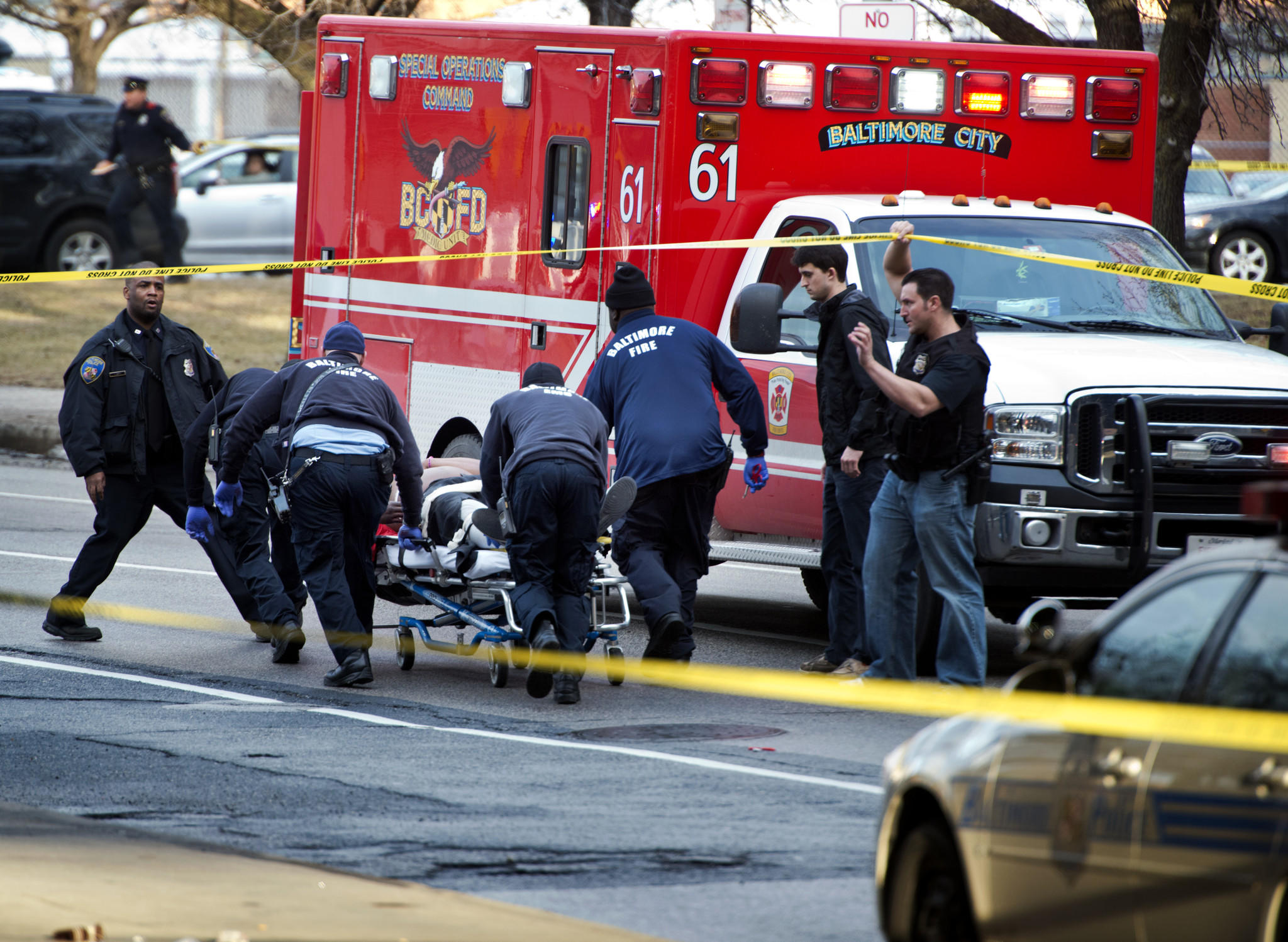 A victim of a shooting is taken to an ambulance on Centre Street. He was under I-83 while awaiting medical attention.