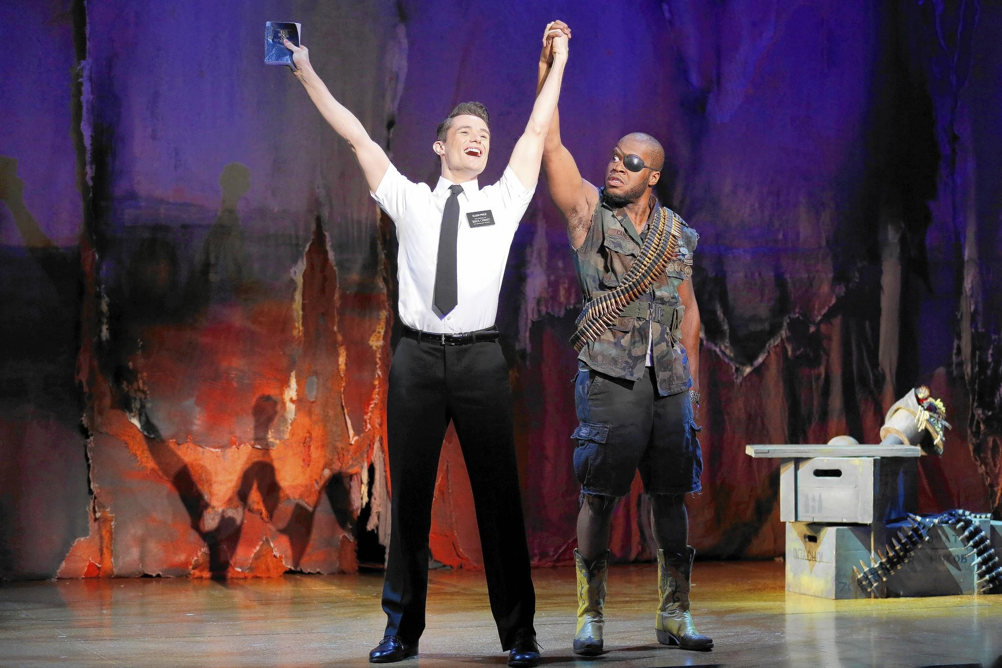 "Mark Evans, left, as missionary Elder Price and Derrick Williams as a Ugandan warlord in ""The Book of Mormon."" The national touring production plays the Hippodrome Feb. 25-March 9"