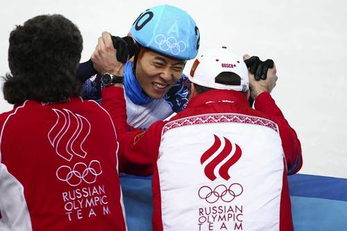 Victor An of Russia celebrates winning the gold medal with his coaches in the Short Track Men's 500m Final A.