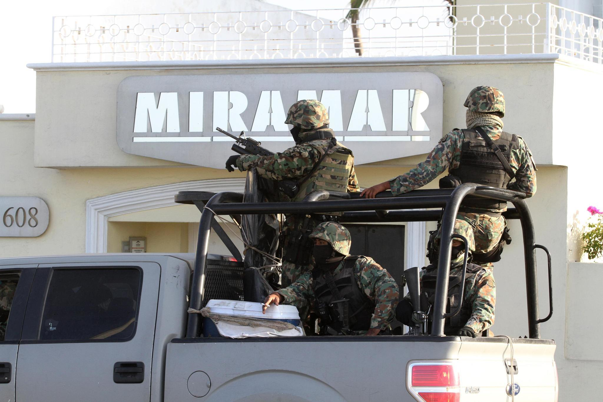"""Military personnel stand atop a truck outside the Miramar building during a raid in Mazatlan. Mexico's most wanted man, drug kingpin Joaquin """"Shorty"""" Guzman, has been captured in Mexico by U.S. and Mexican law enforcement officials, a U.S. government source confirmed on Saturday."""