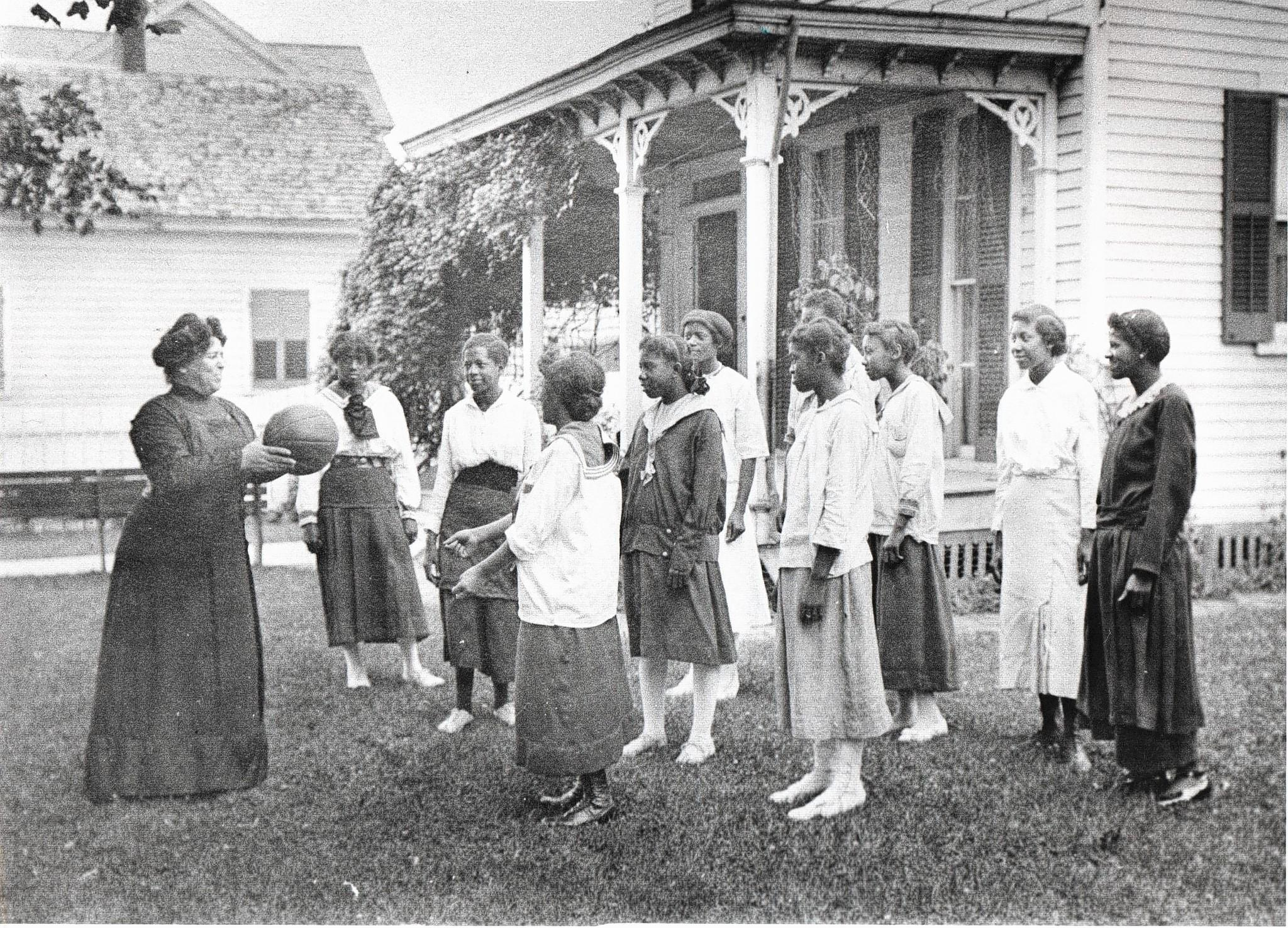 Mrs. Harris Barrett leads a girls' recreation class at Hampton Institute before 1900. Her husband was a president of a bank which was among the nation's largest black-run businesses at the time.