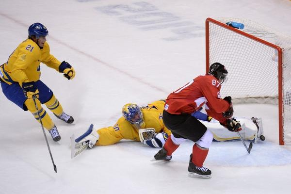 Canada's Sidney Crosby scores past Sweden goalie Henrik Lundqvist as Sweden's Loui Eriksson looks on.