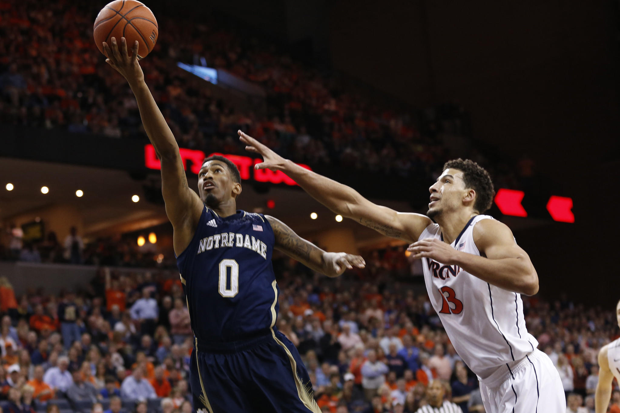 Notre Dame guard Eric Atkins drives past Virginia forward Anthony Gill in the first half.