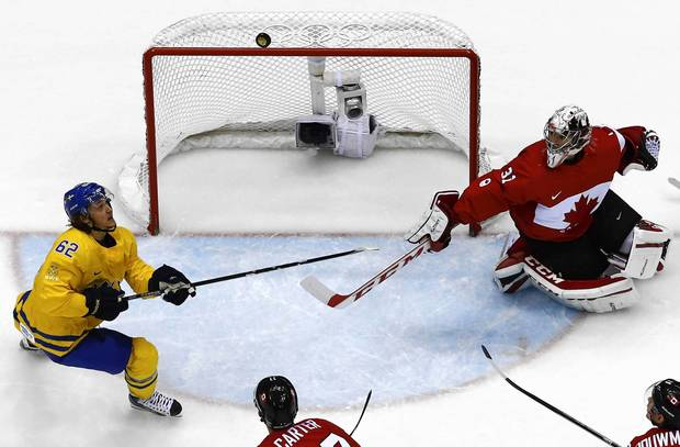 Sweden's Carl Hagelin (62) looks for a loose puck as Canada's goalie Carey Price reacts during the second period of their men's ice hockey gold medal game at the Sochi 2014 Winter Olympic Games.