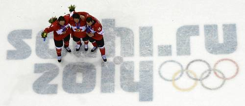 Canada's gold medallists and Chicago Blackhawks Duncan Keith, Patrick Sharp and Jonathan Toews celebrate during the Men's Ice Hockey Medal Ceremony at the Bolshoy Ice Dome.
