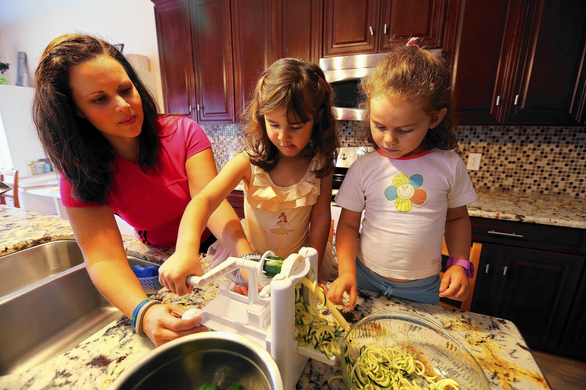 Donni Alvarenga with her twin daughters, Leilani and Zoe, 3, at their Orlando home. They are grating zucchini to make fettuccine alfredo with zucchini pasta.