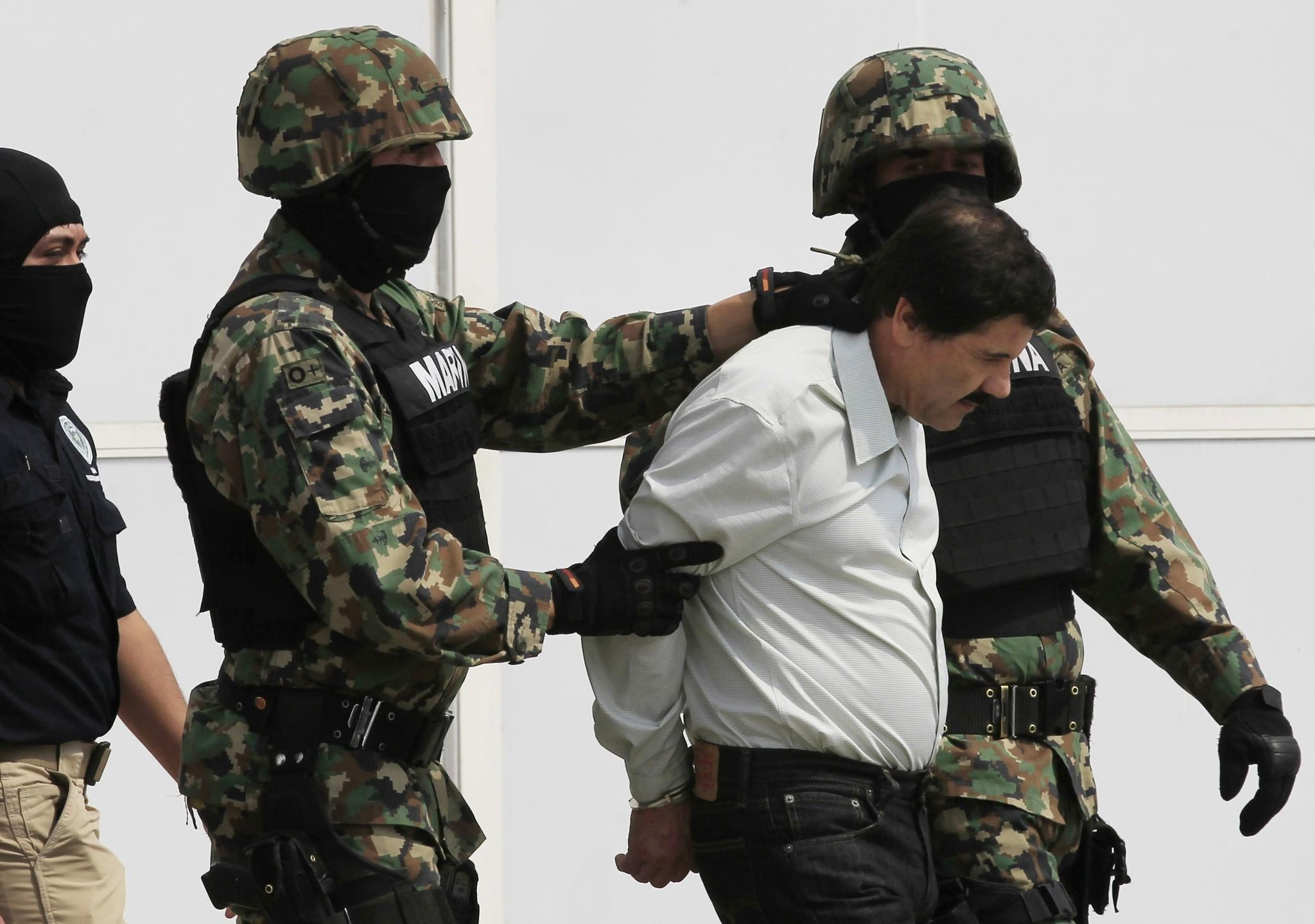 """Joaquin """"Shorty"""" Guzman (R) is escorted by soldiers during a presentation at the Navy's airstrip in Mexico City February 22, 2014. Mexico has captured its most wanted man, drug kingpin Guzman, President Enrique Pena Nieto said via Twitter on Saturday, in a major victory in a long, grisly fight against drug gangs. Guzman, known as """"El Chapo"""" (Shorty) in Spanish, runs Mexico's infamous Sinaloa Cartel and over the past decade emerged as one of the world's most powerful organized crime bosses. REUTERS/Henry Romero (MEXICO - Tags: CIVIL UNREST CRIME LAW DRUGS SOCIETY MILITARY) ORG XMIT: CDG21"""