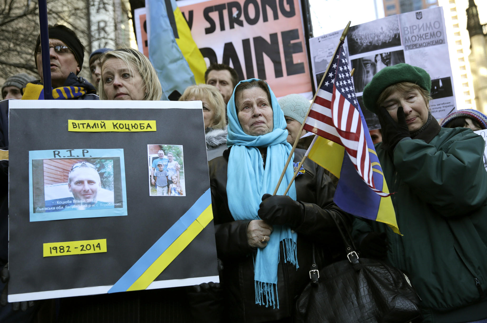 Irene Leseiko-Owerko, left, holds a poster of her cousin, Vitaliy Katsiuba, who was killed during protests in Kiev, as she stands with her mother-in-law Eleonora Owerko, center, and members of Chicago's Ukrainian community during a rally outside the Consulate General of the Ukraine.