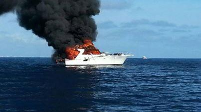 A blaze overtakes the 46-foot Sea Lion Sunday morning. Three passengers were rescued before the boat sank.
