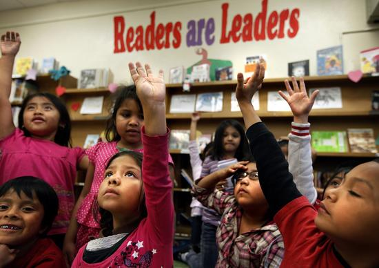 "Raising their hands, Alexa Martinez, 7, back row, left; Jennifer Hernandez, 6; Helen Hernandez, 7; and Noe Ortiz, 6, are eager to answer a question from library aide Cindy Ramirez after reading the book ""Abe Lincoln's Hat"" at San Pedro Elementary School in Los Angeles."