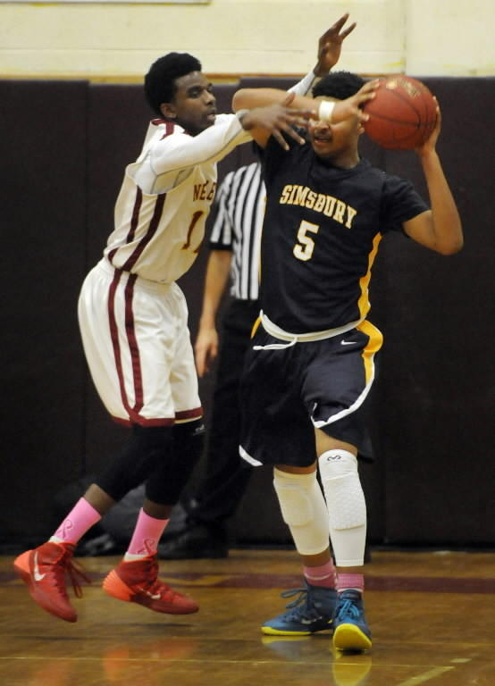 New Britain High School's Curtis Hyman, 12, defends Simsbury High School's EJ Crawford, 5, during the second period. The New Britain High School boys basketball team took on Simsbury High School in a game played in New Britain on Feb. 7.