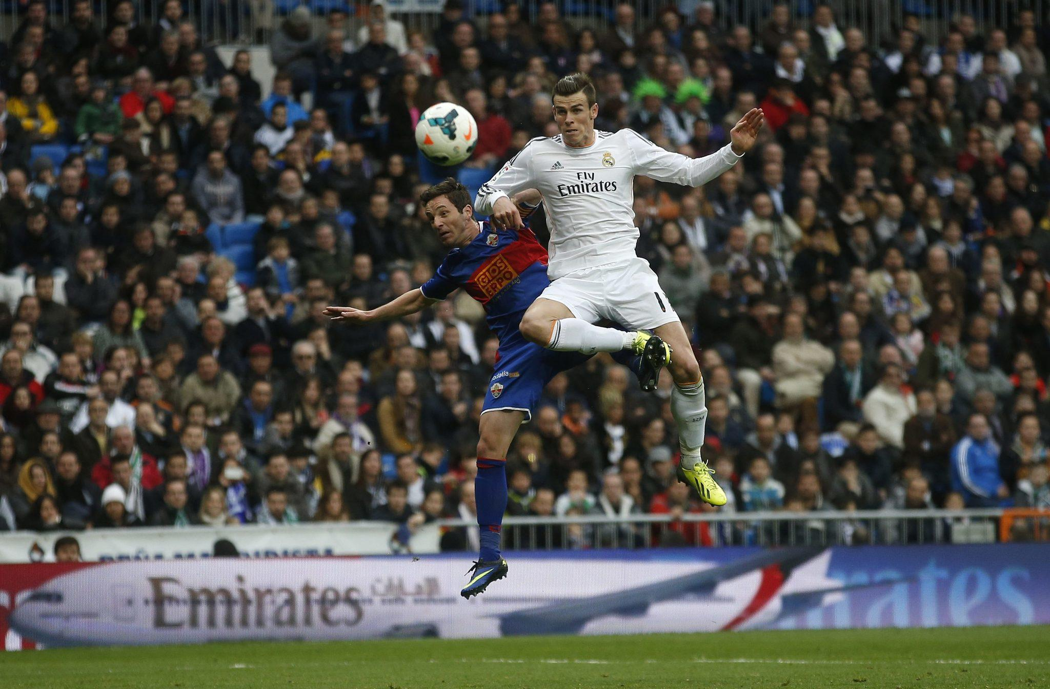 Real Madrid's Gareth Bale jumps with Elche's Edu Albacar (L) during their Spanish first division soccer match against Elche at Santiago Bernabeu stadium in Madrid February 22, 2014.