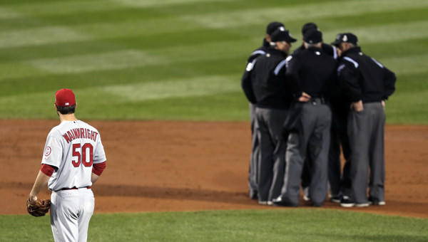 St. Louis Cardinals starting pitcher Adam Wainwright watches as umpires discuss a ruling during Game 1 of the World Series against the Boston Red Sox on Oct. 23. The enhanced use of instant replay in 2014 should make tough calls a little easier to make for umpires.