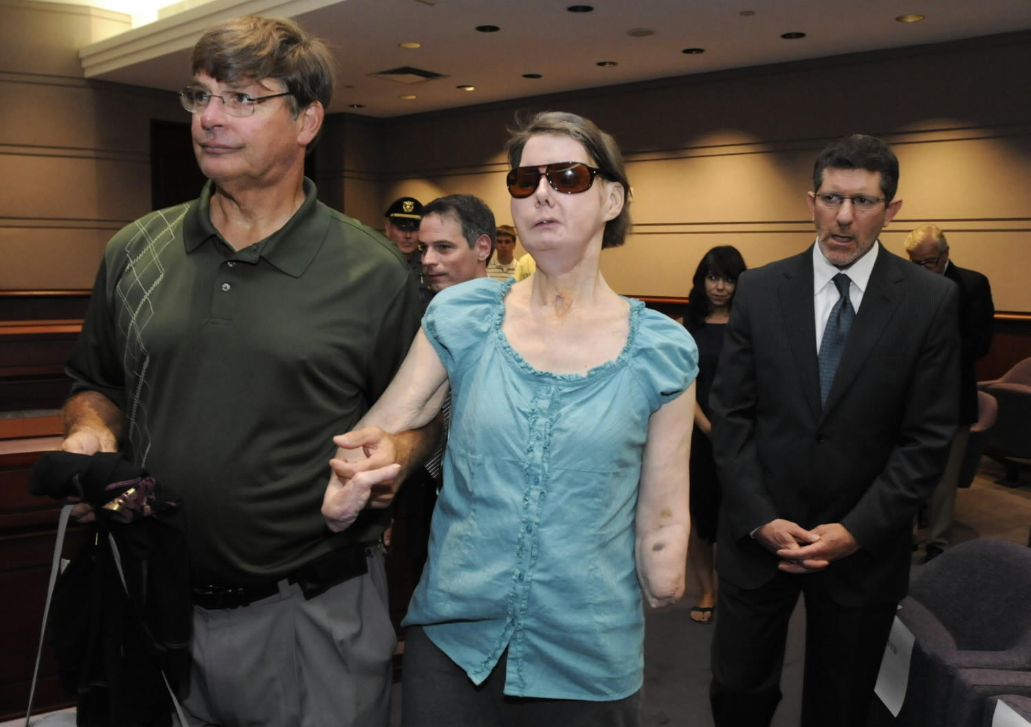 With her brother Steve Nash, left, and attorney Matthew D. Newman, Charla Nash arrives for a hearing with the state claims commissioner in August 2010.