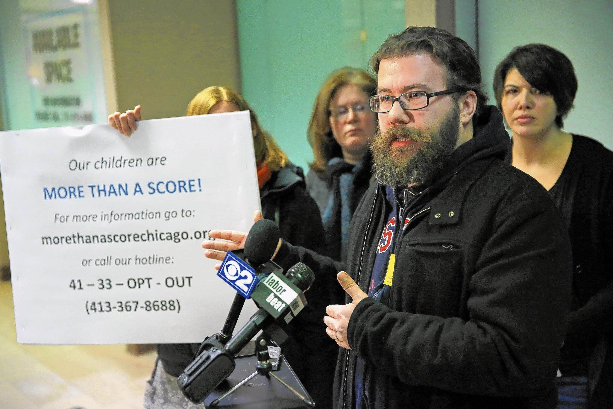 Chris Barrett, right, who has two boys in Drummond Montessori Magnet School, was among those talking about public school students boycotting the Illinois Standards Achievement Test at CPS headquarters on Monday. A new coalition of parent groups is pushing the boycott.