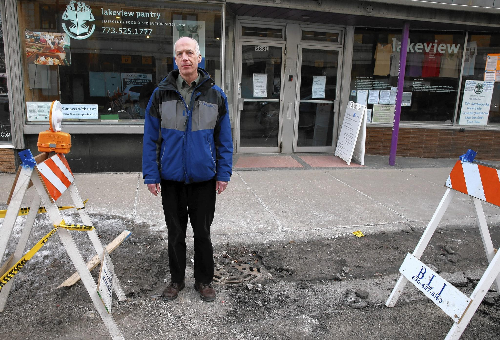 Stuart Iseminger, a director with the Lakeview Pantry, shows part of the street that was dug up so workers could reach the frozen pipe and thaw it.