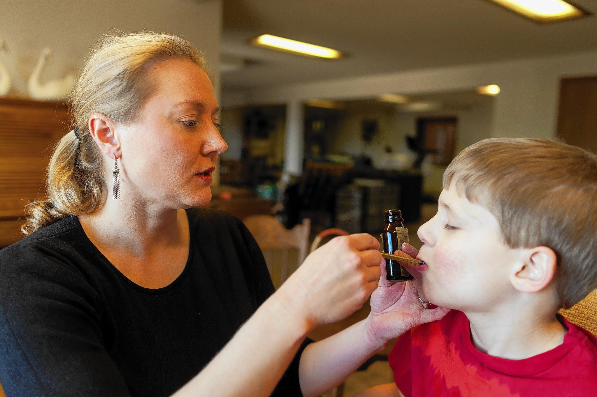 Chase Gross, of Naperville, receives a dose of marijuana-derived medicinal oil from his mother, Nicole, in Colorado Springs, Colo. The Gross family moved away from Illinois, which bans medicinal marijuana for children, to obtain access to the drug for Chase, who has a severe form of epilepsy.