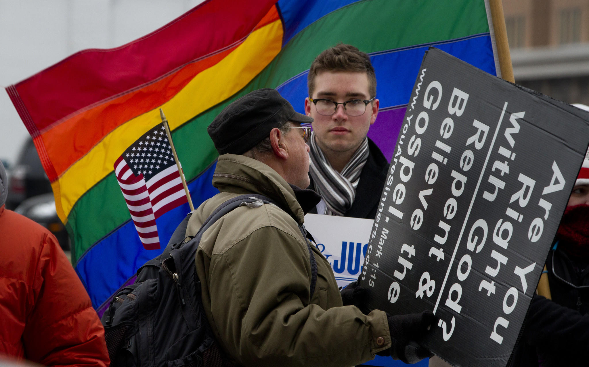 Spencer Geiger, of Virginia Beach, center, stands in support of gay marriage as Don Karns, of Hampton, voices his religious views in opposition to same-sex marriage, as a hearing is underway at the Norfolk federal court on the constitutionality of Virginia's gay marriage ban.