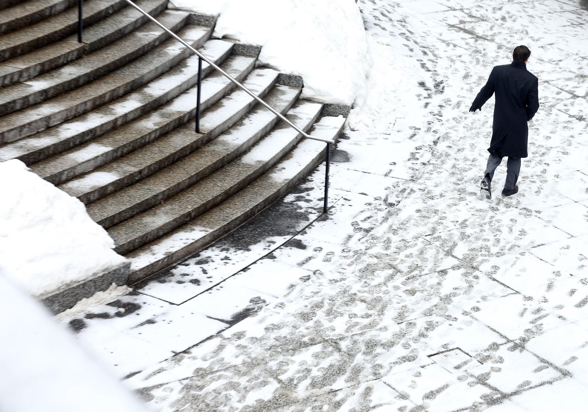 A pedestrians passes through the plaza in front of the John Hancock building after a brief snowstorm.