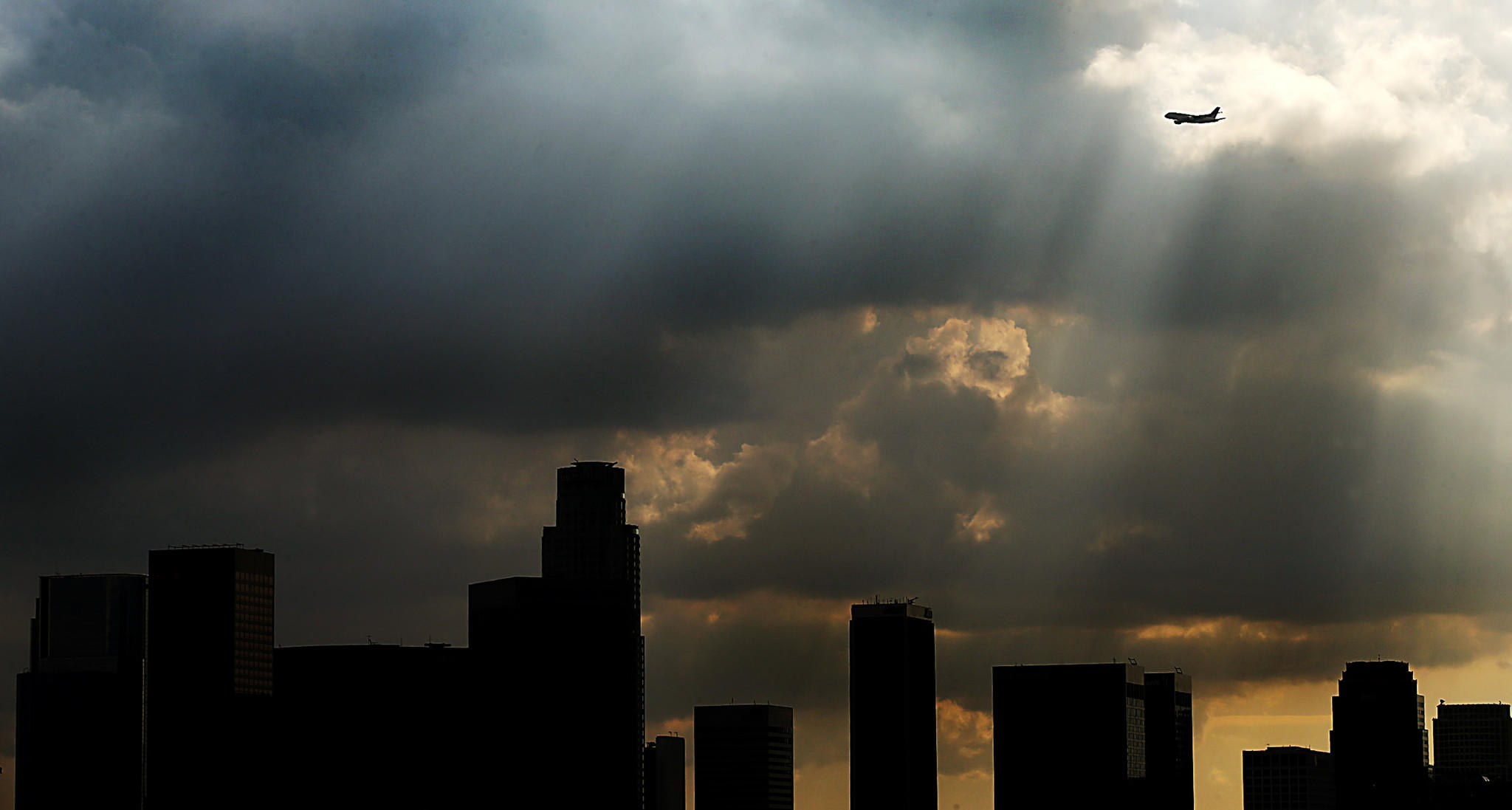 A plane flies into a shaft of sunlight as dark clouds drift inland and over downtown Los Angeles on Friday, Dec. 6, 2013.