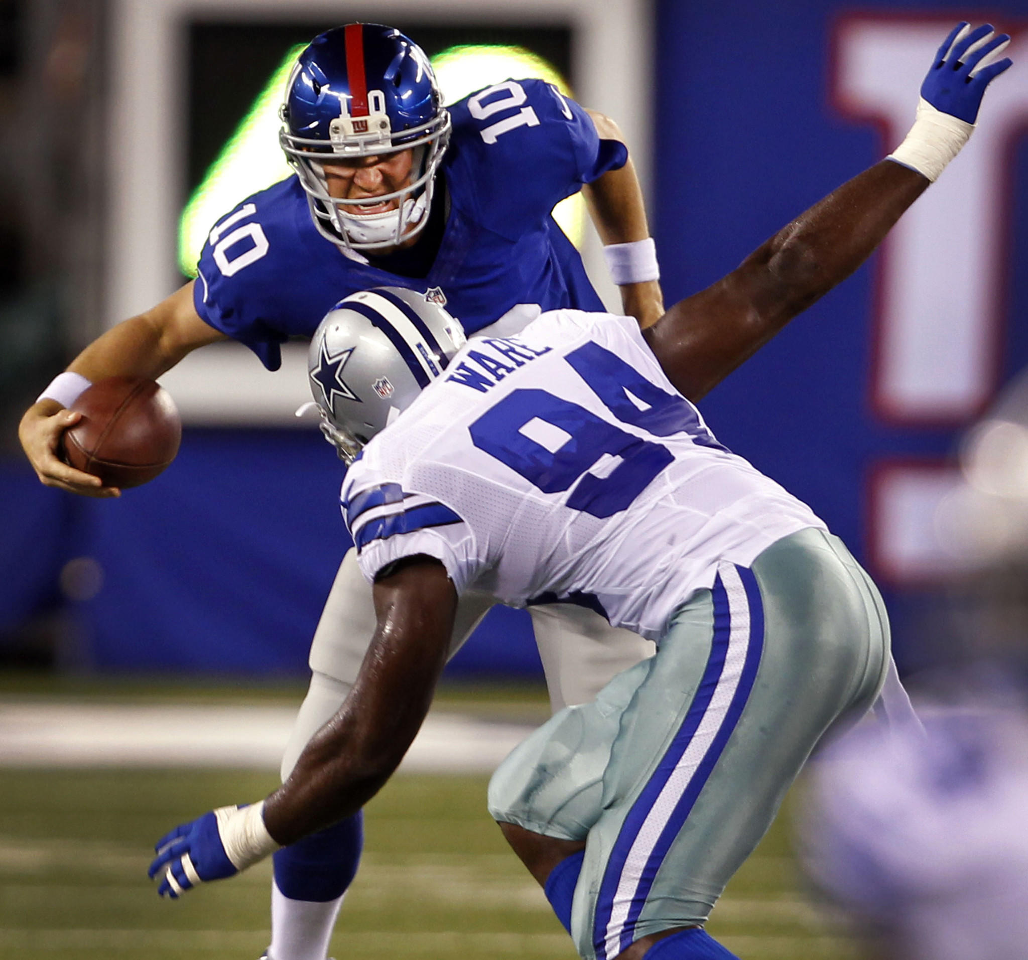 Dallas Cowboys linebacker DeMarcus Ware closes in for the sack on New York Giants quarterback Eli Manning.