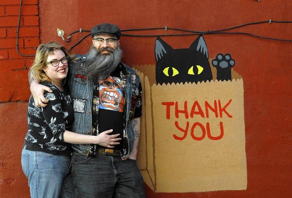 Kate Felder (left) and her husband Mike Podczaski have lived in their Remington house since 2007. Felder painted the black cat in the bag on the side of her house.