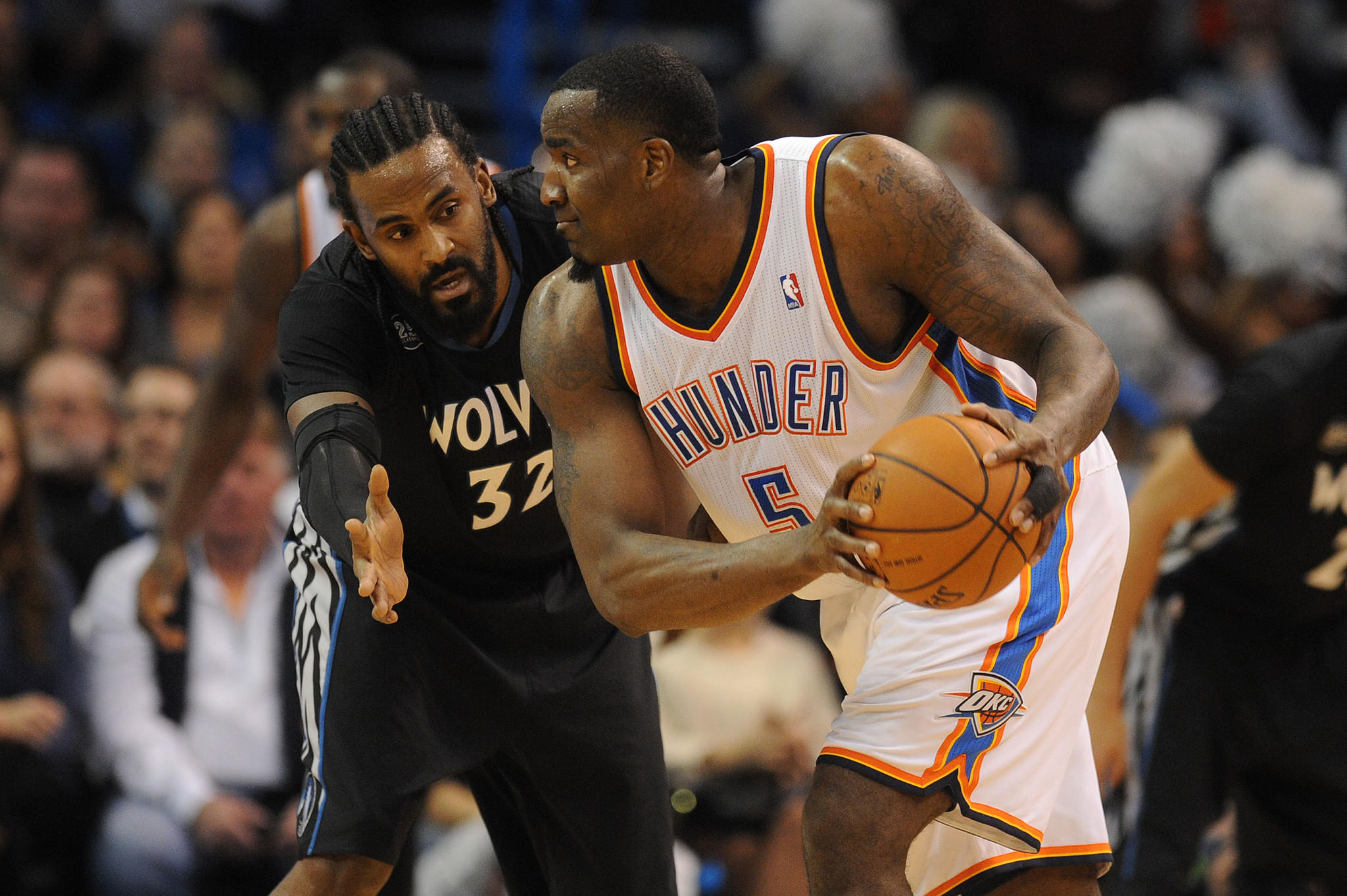 Oklahoma City Thunder center Kendrick Perkins holds the ball as Minnesota Timberwolves center Ronny Turiaf defends.