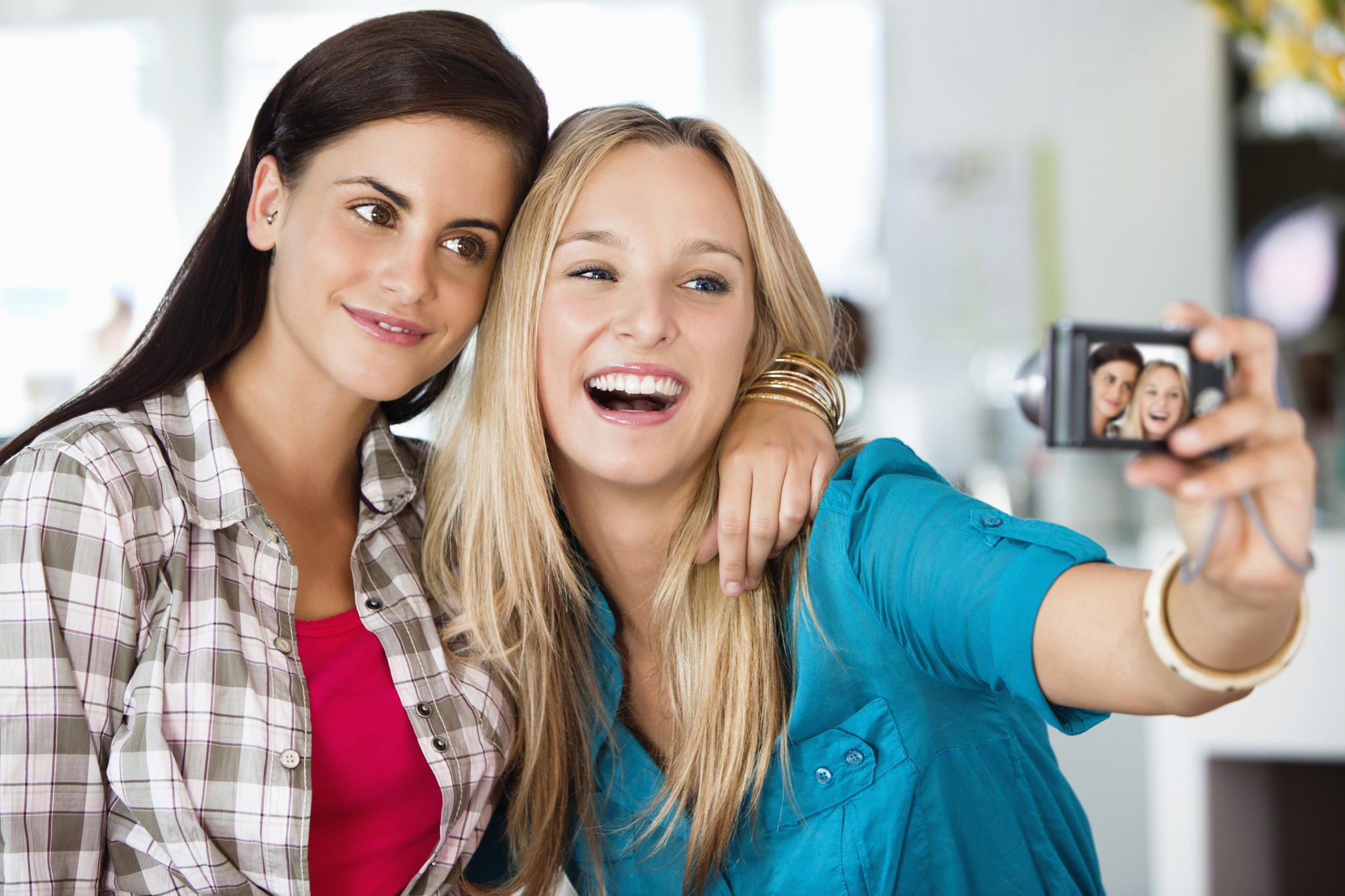 Female friends take a picture of themselves with a camera.