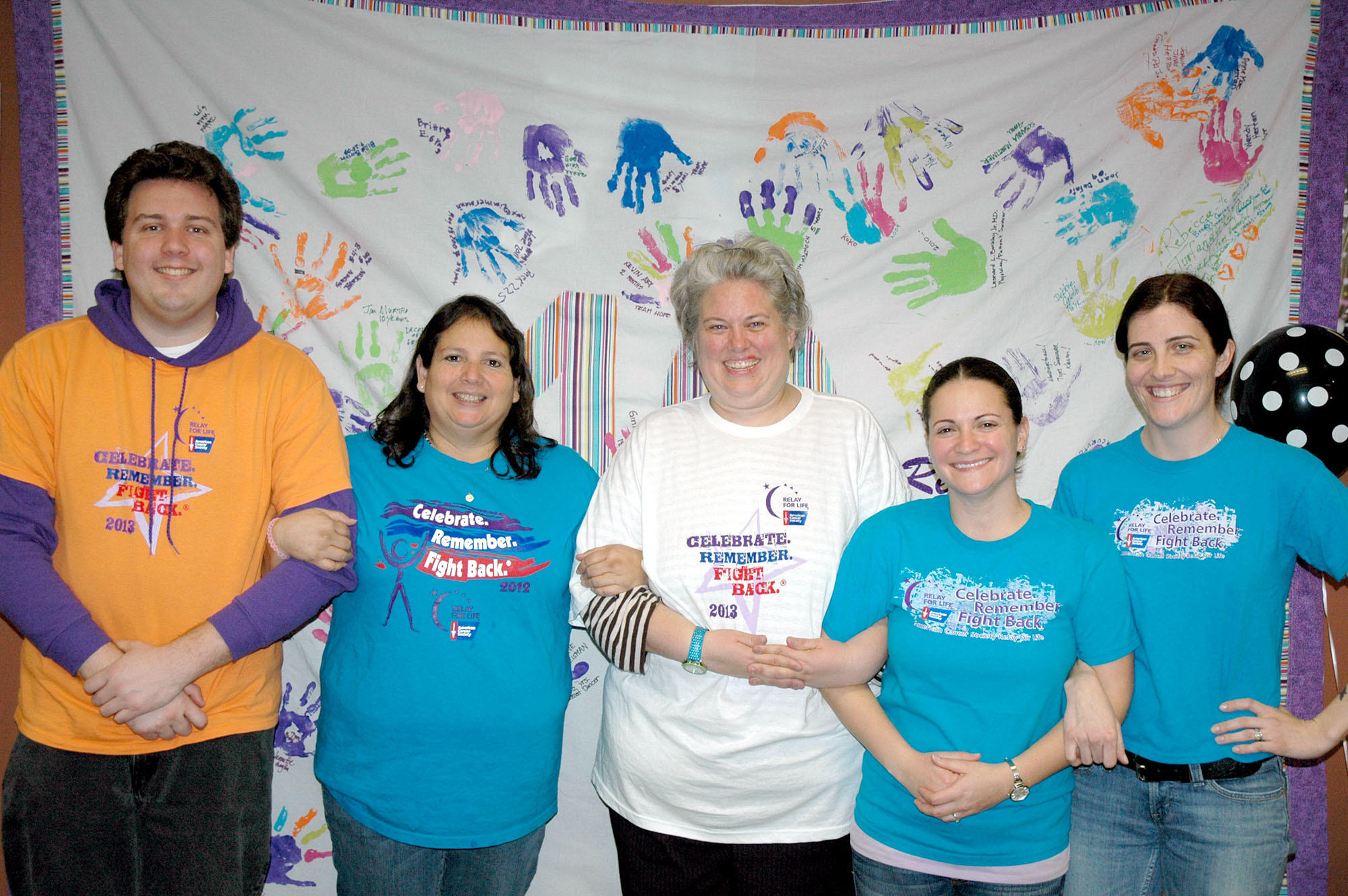 Volunteers for the American Cancer Society's Relay for Life race in Burbank include, from left, Willy Donica, entertainment chair; Michele Higginbotham, team recruitment; Kerry McAloon, community outreach chair; Michelle Leiker, fundraising chair; and Erin Leiker, registration chair. Behind them is the Survivor Blanket created last year.