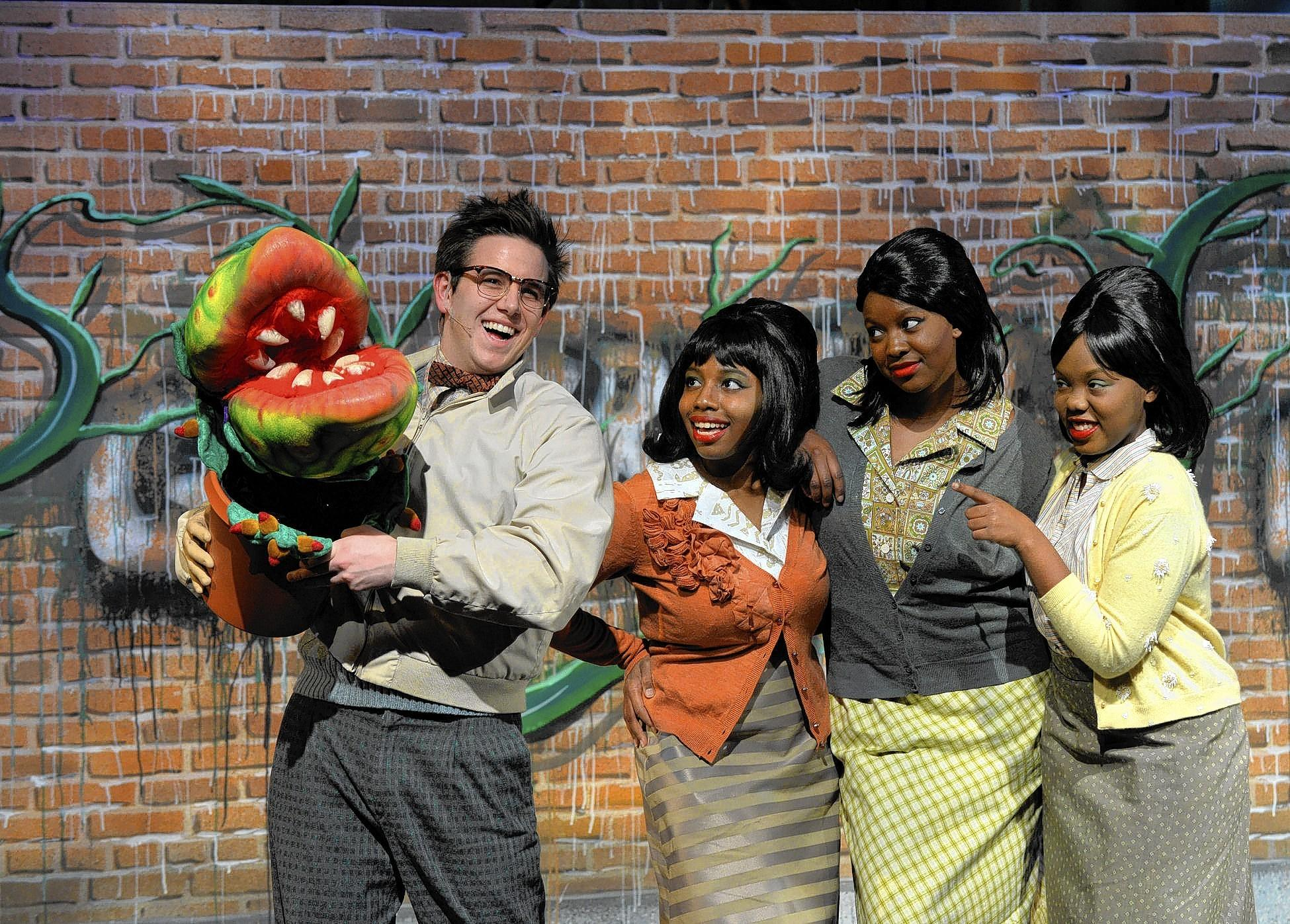 "Kevin Riddagh as Seymour and Bria Boyd, Maria Vincent and Breonna Lewis as the doo-wop trio in Cedar Crest's ""Little Shop of Horrors. """
