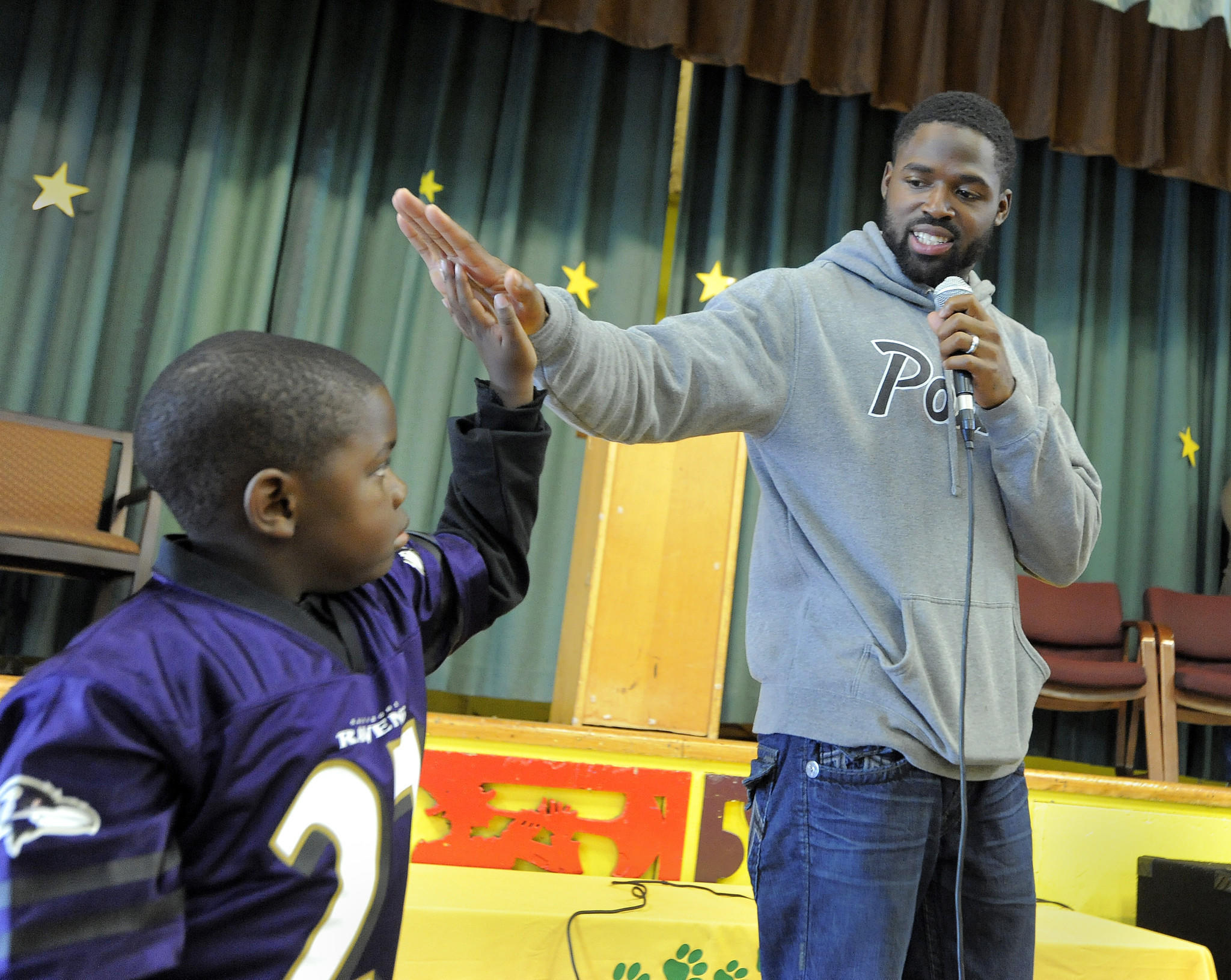 Ravens wide receiver Torrey Smith interacts with a first grader at Gwynn Falls Elementary last October.