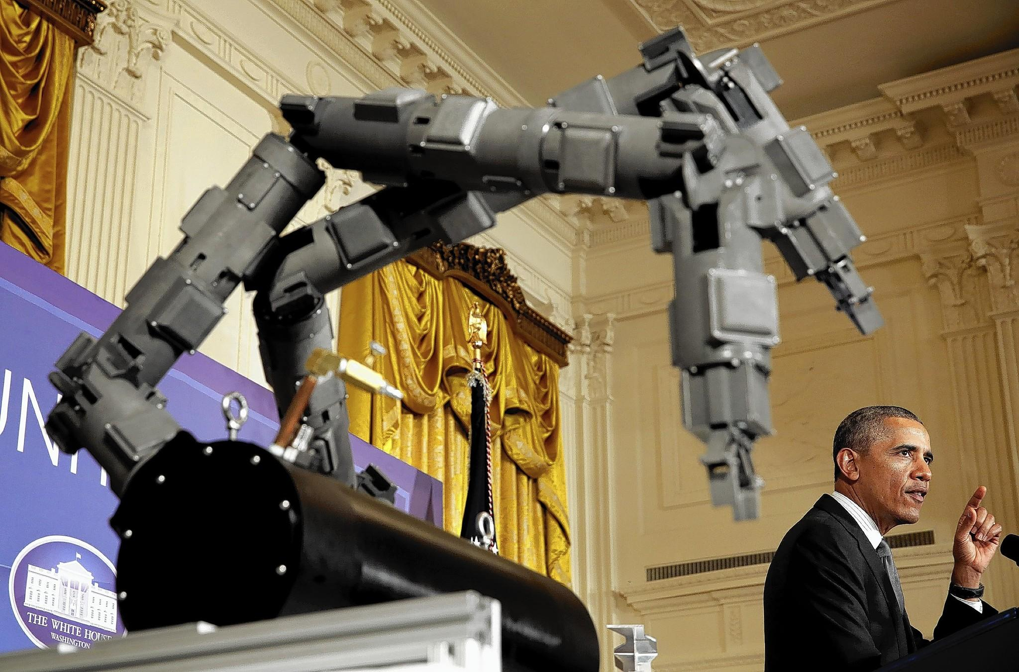 President Barack Obama speaks Tuesday in the White House next to a Navy project, a robotic arm designed to dispose of underwater explosives. Obama officially announced Chicago as the site of one of the two latest innovation institutes.