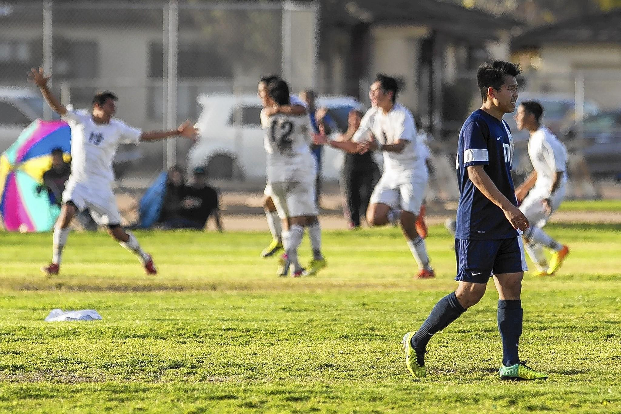 Corona del Mar High's Jake Kim leaves the field as Anaheim celebrates a goal in a sudden-death overtime win during a second round CIF Southern Section Division III playoff game on Tuesday.