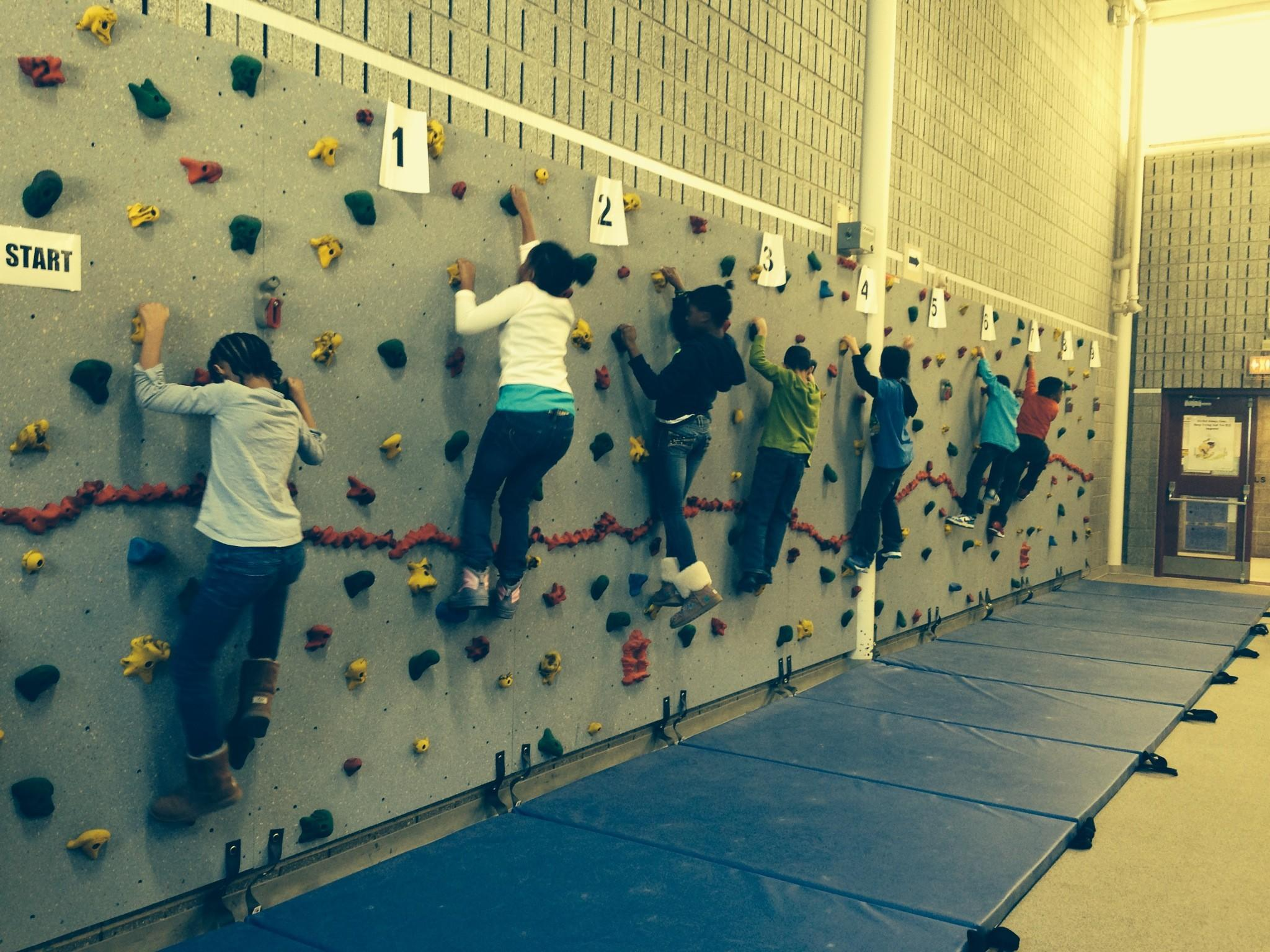 Students at Clover Street School climbing a vertical rock wall that was funded in part by a grant from the Windsor Education Foundation.