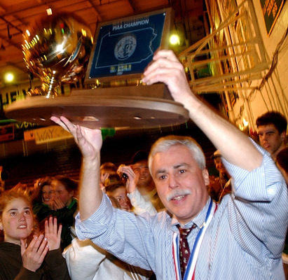 Allentown Central Catholic coach Mike Kopp holds the state championship basketball trophie in a throng of supporters gathered at Rockne Hall in Allentown Saturday night, March 23, 2002. More than 300 fans gathered at the school to welcome the team home from Hershey where they won the state basketball title.
