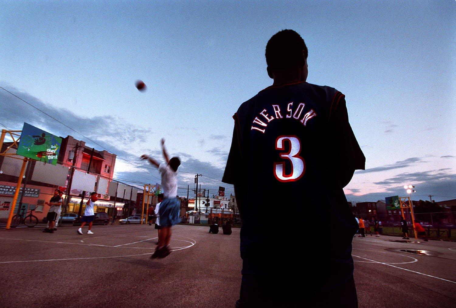 IVERSON FRENZY: Robert Trader, 16, stands on the sidelines of a Capitolo Playground basketball court in the late afternoon light of South Philadelphia waiting for the next pickup game to start. Photo taken May 30, 2001. (Adrin Snider-Newport News-Daily Press)
