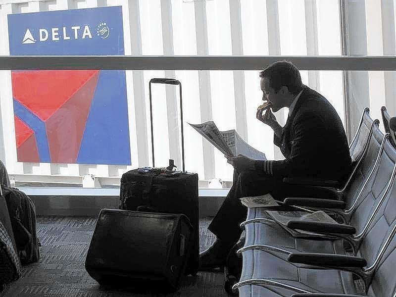 Passenger waits for his flight near a Delta Air Lines logo at Detriot Airport