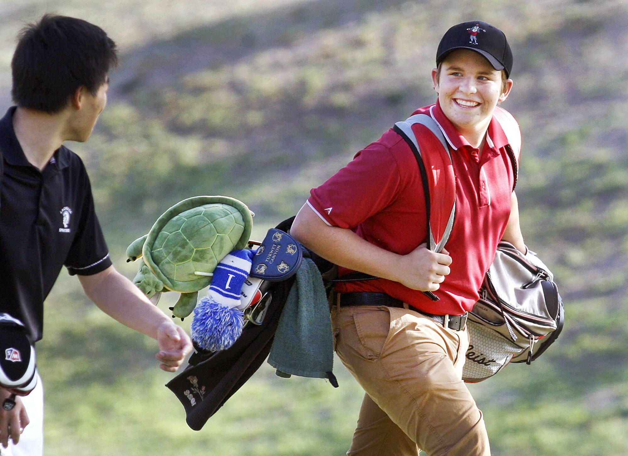 La Cañada's Robby Stehlin smiles to a teammate as he walks to his ball at practice at the La Cañada Flintridge Country Club on Tuesday, February 25, 2014.