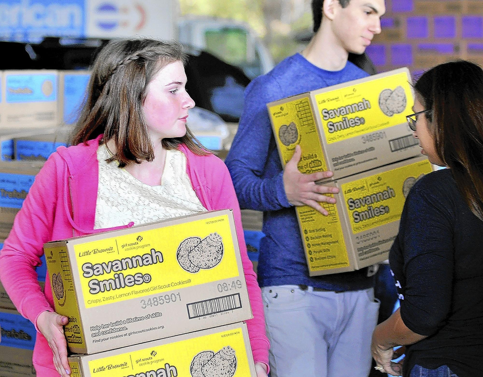 Girl Scout Emily Haug, 15, of Tujunga, helps with loading of cookies at a La Cañada Girl Scout cookie delivery drive-through event at Flintridge Prep. More than 70,000 boxes of Girl Scout Cookies were picked up by more than 80 Girl Scout troop leaders from the Crescenta Valley and Glendale areas on Saturday, Feb. 22, 2014.