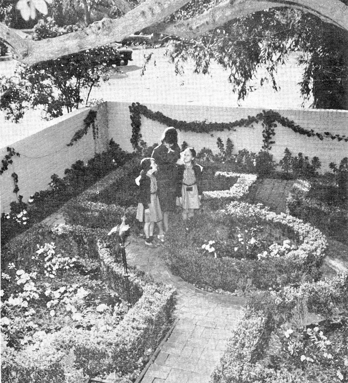 The garden at 384 Meadow Grove Drive in the Flintridge area was included in the 31st annual Girl Scout Garden Tours, a fundraiser for the Pasadena Area Girl Scout Council that was held over a few weekends in the late winter/early spring of 1964. Brownie Scouts Luann Lovejoy and Kathy Wood are shown standing in the garden on Meadow Grove with Senior Scout Marcia Kaech.