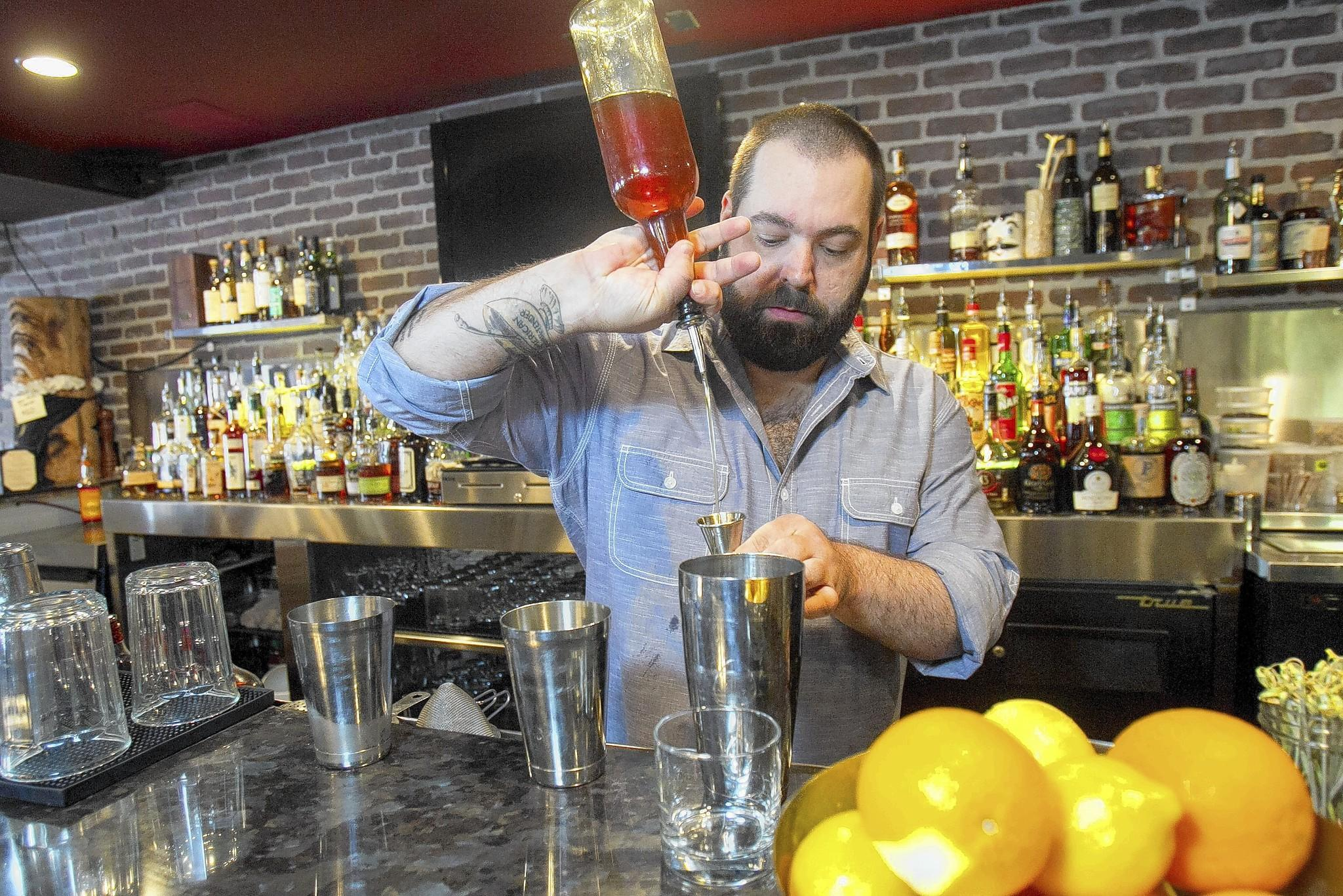 Jason Schiffer, co-owner of 320 Main in Seal Beach, makes a drink called the Detroiter on Tuesday. The restaurant is preparing for the OC Cocktail Week from March 2 to 8.