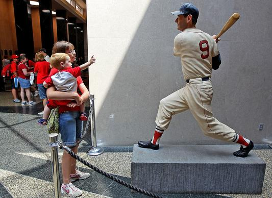 Visitors to the Baseball Hall of Fame and Museum view a statue of Ted Williams during induction weekend in 2010.