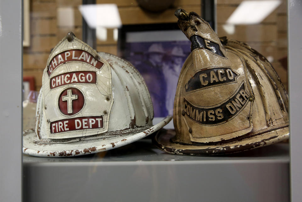 Two helmets on display from a fire chaplain and The Fire Commissioner who is also seen with a hose in his hand in a painting that once hung in city hall right behind the Mayor's desk in council chambers.